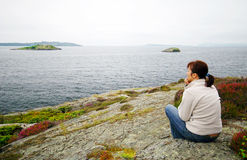 Norwegian sea watching. A woman sitting on a rocky shore of Norwegian Sea, looking on the horizon. Norwegian sea watching stock photo
