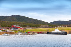 Norwegian small village with colorful wooden houses and ferry Royalty Free Stock Photography