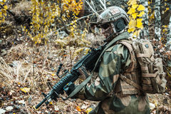 Norwegian soldier in the forest. Norwegian Rapid reaction special forces FSK soldier patrolling in the forest. Field camo uniforms, combat helmet and eye-wear Stock Images