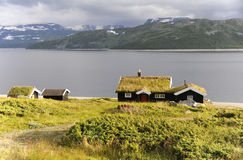 Norwegian Summer. Even in the middle of summer some of the higher mountains in Norway are covered with snow. The roofs of the little houses and huts at Lake Royalty Free Stock Photo