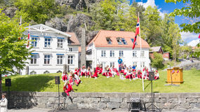 Norwegian teenagers in red dress are resting on the grass Stock Image