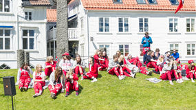 Norwegian teenagers in red dress are resting on the grass Stock Photos