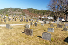 Norwegian tombstones from behind. Drangedal, Norway, March 21, 2015: Traditional Norwegian tombstones on cemetary. Many graves with similar headstones. Early Royalty Free Stock Photography