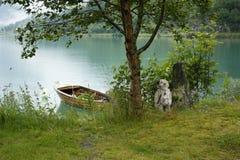 Norwegian Troll and boat. Near the lake Stock Photos