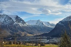 Norwegian valley in winter on a warm an friendly day. Norwegian Valley deeply hidden in the country, featuring a warm light and some houses Stock Image