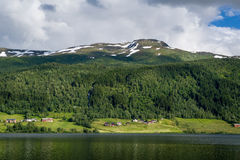 Norwegian village at fjord shore and snowy peaks above. Stock Image