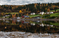 Norwegian wooden house on the fjord shore. Front of colorful autumn forest, Scandinavian style Stock Photography