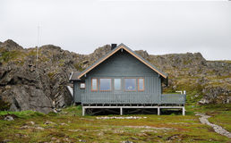 Norwegian wooden house on stilts under cliff Royalty Free Stock Photography