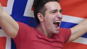 Norwegian Young Man Celebrating while holding the Flag of Norway in Slow Motion. High quality stock photography