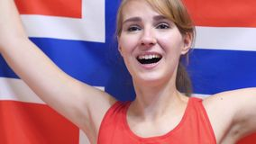 Norwegian Young Woman Celebrating while holding the Flag of Norway in Slow Motion. High quality stock photo