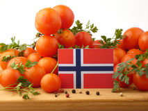 Norwegische Flagge auf einer Holzverkleidung mit den Tomaten lokalisiert auf einem whi lizenzfreies stockfoto