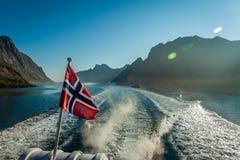 Norwegische Flagge auf Fjord in Lofoten Stockfotografie