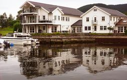 Norwegische weiße Häuser auf dem Ufer des Fjords, klassische skandinavische Architektur stockfoto