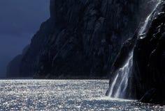 Norwegischer Fjord mit hintergrundbeleuchtetem Wasserfall lizenzfreie stockfotografie