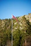 Norwegischer Wimpel auf einem Pfosten mit Bergen Stockbild