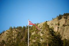Norwegischer Wimpel auf einem Pfosten mit dem Gebirgshintergrund horizontal Stockfotografie