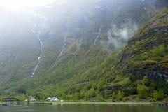 Norwegisches Dorf im Fjord mit Wasserfällen im Hintergrund stockfoto