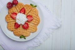 Norwegisches Herz formte die Waffeln, die mit Erdbeeren, Minze und Schlagsahne auf weißer Platte und weißem hölzernem Hintergrund Lizenzfreie Stockfotos