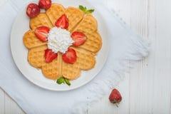 Norwegisches Herz formte die Waffeln, die mit Erdbeeren, Minze und Schlagsahne auf weißer Platte und weißem hölzernem Hintergrund Lizenzfreie Stockfotografie