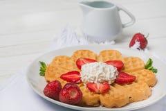 Norwegisches Herz formte die Waffeln, die mit Erdbeeren, Minze und Schlagsahne auf weißer Platte und weißem hölzernem Hintergrund Lizenzfreie Stockbilder