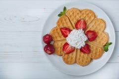 Norwegisches Herz formte die Waffeln, die mit Erdbeeren, Minze und Schlagsahne auf weißer Platte und weißem hölzernem Hintergrund Lizenzfreies Stockfoto