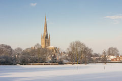 Norwich Cathedral in winter. View of Norwich Cathedral across snowy cricket field Stock Photo
