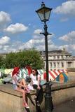 NORWICH UK - JUNI 3, 2017: Två brittiska unga kvinnor som tycker om en solig dag på minnes- trädgårdar med de färgrika stallsna a Fotografering för Bildbyråer