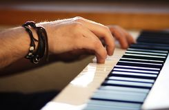 Nos homens do instrumento do teclado as mãos pressionam as chaves fotografia de stock
