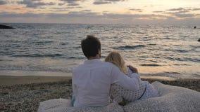 Nos pares do amor que relaxam em descansos grandes perto do oceano video estoque