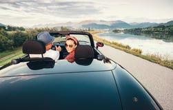 Nos pares do amor que viajam pelo carro do cabriolet Fotografia de Stock