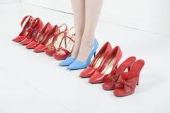 Nos saltos altos azuis entre sapatas vermelhas Imagens de Stock Royalty Free