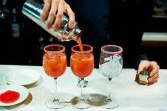 Nos vidros com gelo o empregado de bar derrama cocktail imagens de stock royalty free
