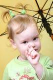 Nose. Funny little girl under yellow umbrella Stock Photos