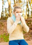Nose blowing. Young beautiful woman suffering from influenza, blowing her nose in handkerchief Royalty Free Stock Photography