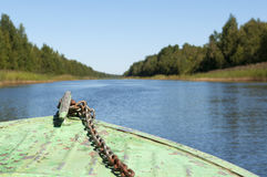 Nose boat. Stary boat moves through the channel. Rusty chain. Clear blue sky and blue water Royalty Free Stock Photo