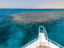 The nose, the front of the white yacht, the boat, the ship standing on the jig, parking, anchoring in the sea, the ocean with blue. Water with coral reefs stock photography