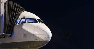 Nose of Jet Liner night at Gate waiting for boarding. Black Copyspace Stock Image