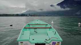 Nose of mint boat on the Lake Annecy against the background of fog mountains. Close up. 4k stock video