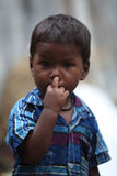 Nose Picking Boy. A poor little boy in blue shirt from India picking his nose Royalty Free Stock Photos