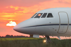 Nose of a private business jet. On the runway with the sun in the background Stock Photos