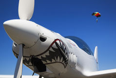 Nose and propeller. Of a white aeroplane in a blue sky and a parachute Royalty Free Stock Photography