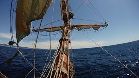 On nose of replica vintage ship sailing in open sea. View from nose of old vintage sailing ship waving in deep blue sea with ropes and maintenance thing in air stock video footage