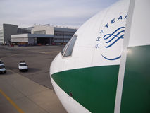 Nose of a SkyTeam Aircraft. Nose of the boeing 777 airplane, closeup shot.This plane is member of sky team alliance. A big hangar is on background Stock Photos