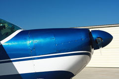 Nose of small airplane. The nose and propeller from a light airplane (Cessna 180) is in front of a hangar at an airport. Plane is white and blue and was built in stock images