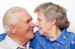 Nose to nose. Happy old couple look each other eyes nose to nose. over white Stock Photography