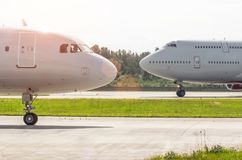 Nose to nose two planes on the runway at the airport. Royalty Free Stock Photo
