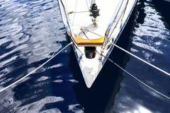 Nose yachten med rep på skeppsdockan i det blåa vattnet Arkivbild