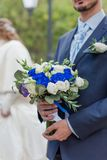 Nosegay in hands of bridegroom. Man in suit and stylish tie is holding wedding bouquet from white and blue roses royalty free stock photo