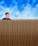 Nosey Neighbor Man Looking Over Fence. A nosy neighbor is looking over a fence in a backyard at something with shock and surprise on his face for a secret or Stock Images