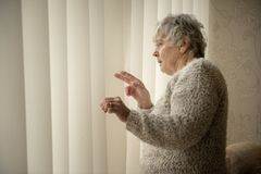 Nosey neighbour, senior woman looking through window royalty free stock images